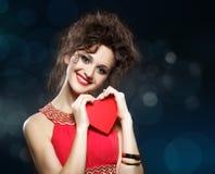 A menina no vestido vermelho mantém o coração. Conceito do dia de Valentim foto de stock