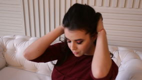 Menina no vestido vermelho que senta-se em um sofá do couro branco Vídeo cheio de HD vídeos de arquivo
