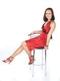 Menina no vestido vermelho que senta-se na cadeira Fotografia de Stock Royalty Free