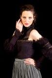 Menina no vestido vitoriano escuro com mão além de seus olhos Foto de Stock