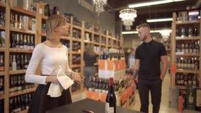 Menina no vidro de vinho de fricção da camisa branca e da saia preta em uma loja de vinho O homem com tatuagem andou acima à meni vídeos de arquivo