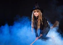 Menina no voo do chapéu da bruxa no cabo de vassoura. Imagem de Stock