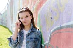 A menina nos óculos de sol aproxima a parede dos grafittis Imagens de Stock Royalty Free