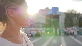 A menina nos óculos de sol com o móbil no close-up do braço, mulheres nos vidros olha imagens telefona fora, vídeos de arquivo