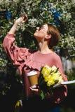 Menina nos óculos de sol e em vidros cor-de-rosa da camiseta com entre as árvores de florescência fotografia de stock royalty free