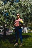 Menina nos óculos de sol e em vidros cor-de-rosa da camiseta com entre as árvores de florescência fotos de stock