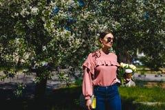 Menina nos óculos de sol e em vidros cor-de-rosa da camiseta com entre as árvores de florescência foto de stock royalty free