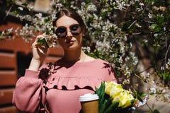 Menina nos óculos de sol e em vidros cor-de-rosa da camiseta com entre as árvores de florescência imagens de stock
