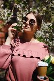 Menina nos óculos de sol e em vidros cor-de-rosa da camiseta com entre as árvores de florescência imagens de stock royalty free