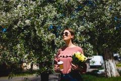 Menina nos óculos de sol e em vidros cor-de-rosa da camiseta com entre as árvores de florescência foto de stock