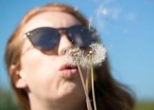 A menina nos óculos de sol funde o dente-de-leão ausente fotos de stock