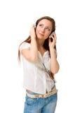 A menina nos auscultadores escuta a música que olha acima Fotos de Stock