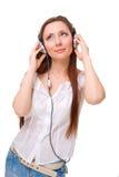 A menina nos auscultadores escuta a música que olha acima Imagens de Stock Royalty Free