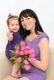 Menina nos braços de sua mãe. Mantenha flores fotografia de stock royalty free