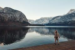 A menina nos cervos traja a montanha enorme com reflexão e o lago na central de Europa Foto de Stock
