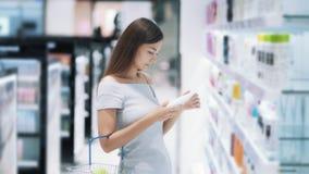 A menina nos cosméticos compra escolhe de creme, olha bens, põe-no sobre a prateleira, movimento lento vídeos de arquivo