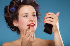 Menina nos encrespadores de cabelo que aplicam o batom vermelho Imagens de Stock Royalty Free