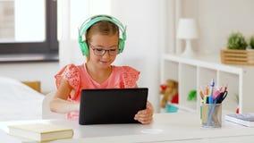 Menina nos fones de ouvido com tablet pc em casa video estoque