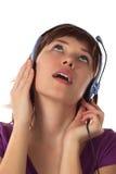 A menina nos fones de ouvido escuta a música imagens de stock royalty free