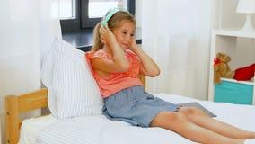 Menina nos fones de ouvido que escuta a música no PC da tabuleta filme