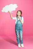 Menina nos macacões da sarja de Nimes que guardam a bolha vazia do discurso e que pensam no rosa Fotos de Stock