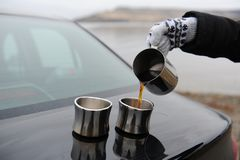 A menina nos mitenes derrama o café do jarro nos copos no tronco de carro r Foto de Stock