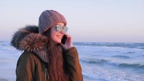 A menina nos monóculos comunica-se pelo telefone fora em férias na costa de mar video estoque