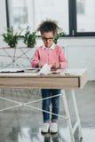 Menina nos monóculos que cortam a folha de papel com tesouras ao estar na tabela do escritório Fotografia de Stock