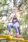 Menina nos obstáculos da passagem do parque da corda, escalada da menina a estrada Parque da corda imagens de stock royalty free