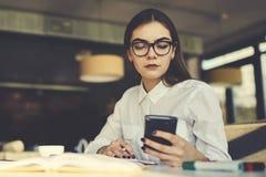 Menina nos peritos do funcionamento de vidros que fornecem a campanha de publicidade no Web site popular através do smartphone fotografia de stock royalty free