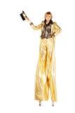 Menina nos pernas de pau vestidos no ouro Fotografia de Stock