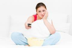 Menina nos pijamas com tevê do controlo a distância fotos de stock