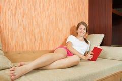 Menina nos shorts que lê no sofá Imagem de Stock Royalty Free