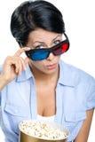 Menina nos vidros 3D que olha o filme com a bacia de pipoca Imagens de Stock