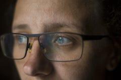 Menina nos vidros com os olhares dos olhos azuis ausentes imagens de stock royalty free