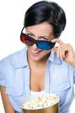 Menina nos vidros 3D que olha o filme com pipoca Fotografia de Stock Royalty Free