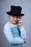 Menina nos vidros e no chapéu negro Fotografia de Stock