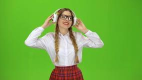 A menina nos vidros escuta a música em fones de ouvido Tela verde video estoque