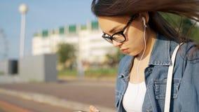 A menina nos vidros põe sobre os fones de ouvido brancos A morena na rua introduz um fone de ouvido em sua orelha video estoque