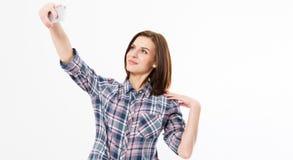 A menina nova alegre do estudante com trouxa faz o selfie em seu telefone celular, em retrato do estúdio da mulher bonita que sor fotos de stock royalty free