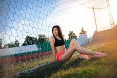Menina nova, atlética, 'sexy' que senta-se na grama de um estádio de futebol perto do objetivo do futebol Fêmea bonita menina des imagens de stock royalty free