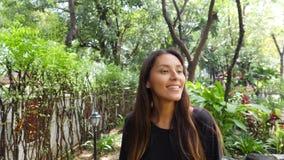 Menina nova atrativa do turista da raça misturada que aprecia o passeio no parque com plantas e as árvores exóticas 4K, Slowmotio filme