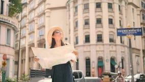 Menina nova atrativa do turista que está na rua velha com mapa e olhar da cidade ao redor 4k, movimento lento video estoque