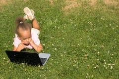 Menina nova bonita da raça misturada que usa o portátil Imagem de Stock Royalty Free