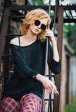 A menina nova bonita da rocha do grunge que veste a saia quadriculado, a camiseta e os vidros senta-se na escadaria e no cigarro  imagens de stock