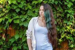 Menina nova bonita de brunete do moderno com cabelo verde longo que sorri no fundo do parque imagens de stock