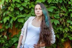 Menina nova bonita de brunete do moderno com cabelo verde longo que sorri no fundo do parque foto de stock