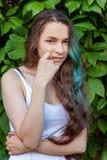 Menina nova bonita de brunete do moderno com cabelo verde longo que sorri no fundo do parque foto de stock royalty free