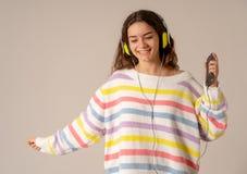 Menina nova bonita do adolescente nos fones de ouvido que escuta a música e a dança isolada no fundo cinzento imagem de stock royalty free