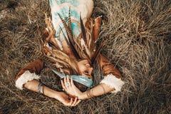 Menina nova bonita do boho no revestimento que encontra-se para baixo na grama Foto de Stock